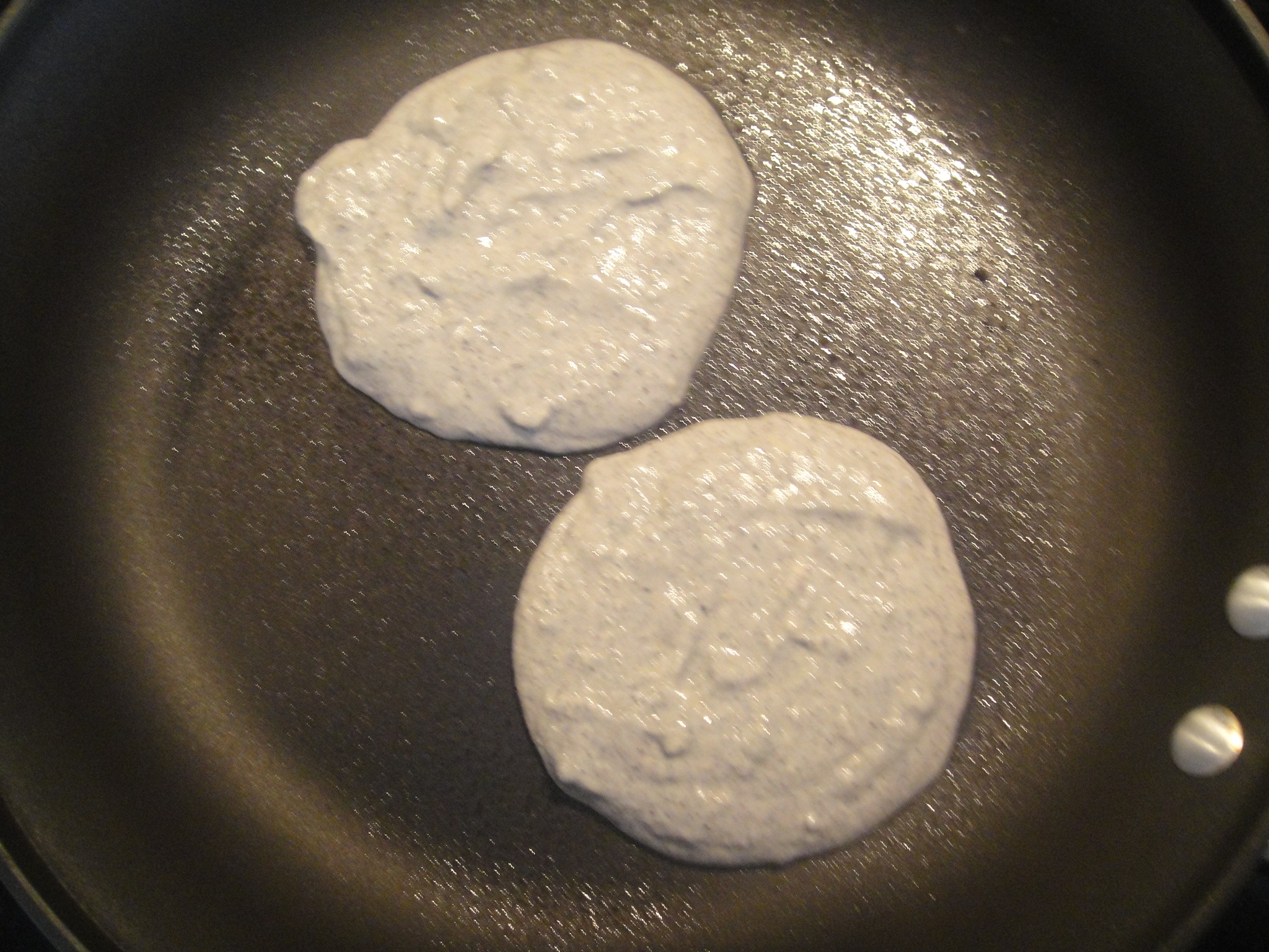 two blue corn pancakes in pan